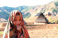 A girl before a house in a mountain village in the scenery with poor bites of the mountain region to the south of Dili of the capital of the east Timo...