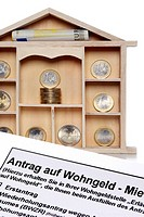 Miniature house with euro coins and application form for home assistance