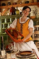 Young woman presenting roast goose, rustic