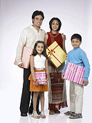 South Asian Indian family with father mother son and daughter carrying packet of shopping and looking at camera MR 698 , 699 , 700 , 701