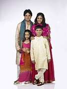 South Asian Indian family with father mother son and daughter standing smiling and looking at camera MR 698 , 699 , 700 , 701