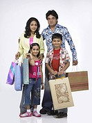 South Asian Indian family with father mother son and daughter standing with carrying shopping bags MR 698 , 699 , 700 , 701