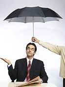 South Asian Indian executive extend hand palm up sitting under umbrella looking above MR702A