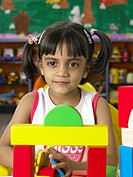 South Asian Indian girl sitting in front of toys in nursery school MR