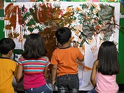 South Asian Indian boys and girls doing painting on board in nursery school MR