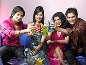 South Asian Indian men and women toasting drink glasses celebrating party MR