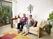 Old couple showing white mugs sitting on sofa MR702T,702S