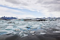 Ice floes in the Joekulsarlon glacier lake, different colours due to volcanic ash, in the back the Vatnajoekull glacier, Joekulsárlón, Vatnajoekull, I...