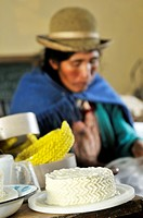Production of fresh cheese in the Penas Valley, finished cheese and woman in traditional dress of the Quechua in the Departamento Oruro, Bolivia, Sout...