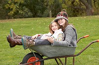 Two Sisters Sitting In Wheelbarrow Outdoors