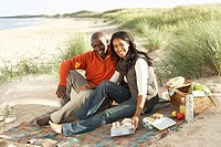 Young Couple Enjoying Picnic On Beach Together