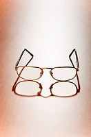 Reading glasses on the wooden background