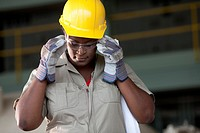 Black worker in hard_hat adjusting protective eyewear