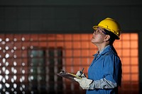 Chinese worker in hard_hat holding clipboard