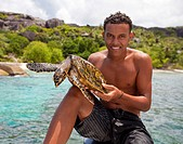 Creole Guide holding a sea turtle, Seychelles, Africa, Indian Ocean