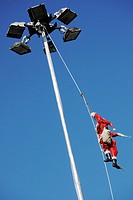 Pere Noel climbs up light pole