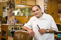 Hispanic barber standing in barbershop