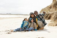 Family Sitting On Winter Beach