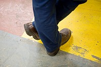 Factory worker wearing protective boots, standing with legs crossed at ankle, cropped