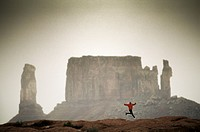 Man Running Along Rocky Terrain With Butte in Background, Moab Desert, Utah, USA