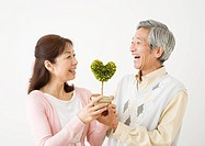 Senior couple holding potted plant