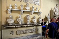 Tour guide in front of bust statues in the Vatican Museum, Italy