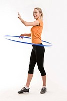 Energetic woman having workout with blue hoop in hands