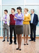 Company of business partners standing and turning their heads aside with serious woman in front