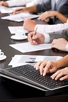 Photo of females hands touching keys of laptop during briefing on background of human hands holding pens with papers and cups near by