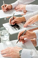 Hands of three business people over the documents lying on the table with a glass of water near by