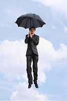 Portrait of businessman under umbrella on the background of cloudy sky