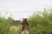 Portrait of a woman on safari looking through her binoculars, Luangwa Valley, Zambia