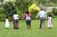 Family holding hands and walking away, Harare, Zimbabwe