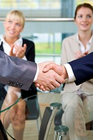 Photo of handshake of business partners on background of applauding females