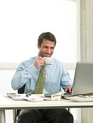 Businessman at desk drinking coffee