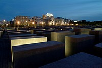 Holocaust Memorial designed by architect Peter Eisenman, memorial to the murdered jews of Europe, with a view of the skyline of the Potsdamer Platz sq...