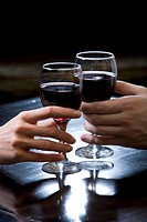 Two hands holding red wine glasses over the black table