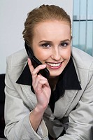 Smiling blond business lady in fashion gray suit is talking by her cell phone