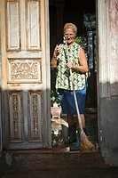 Old woman sweeping the street in front of her house, Baracoa, Guantanamo, Cuba, Caribbean
