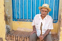 Old man with a walking stick sitting down in the street, Trinidad, Sancti Spiritus, Cuba, Caribbean