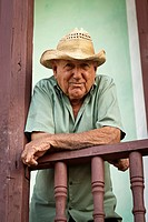 Old man with straw hat on his verandah , Trinidad, Sancti Spiritus, Cuba, Caribbean