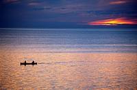 Two men canoeing on Lake Superior at sunset