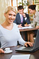 Confident business woman in white blouse sitting at the table with cup, laptop, paper on it