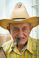 Old man with a cigar and a straw hat with political badges, Trinidad, Sancti Spiritus, Cuba, Caribbean