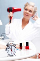 Image of alarm clock on background of female drying her hair