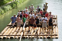 Group of tourists on wooden raft, Isar River, Munich, Bavaria, Germany