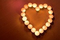 Candles arranged in heart shape on wooden floor