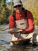 Woman holds and shows off a Rainbow Trout caught while fly fishing on the Russian River, Kenai Peninsula, Southcentral Alaska, Autumn