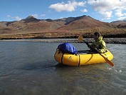 Woman packrafts down the Sanctuary River in Denali National Park, Interior Alaska, Autumn