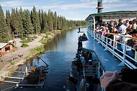 Tourists on board the Riverboat Discovery view the Chena Indian Village, a mock_village on the Riverboat Discovery tour along the Chena River, Fairban...